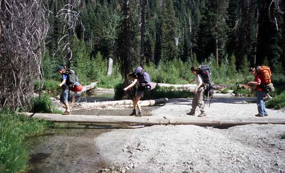 String of backpackers crossing a creek on a log